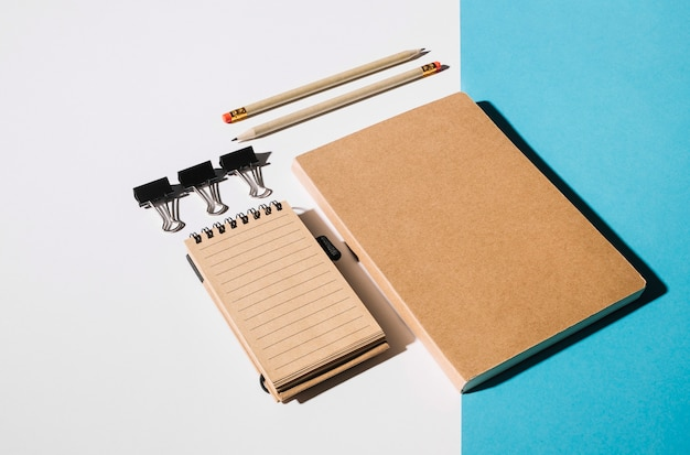 Bulldog clip; pencil and closed book on dual background Free Photo