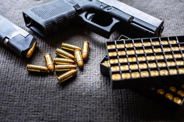 Bullets and gun on black velvet desk Premium Photo