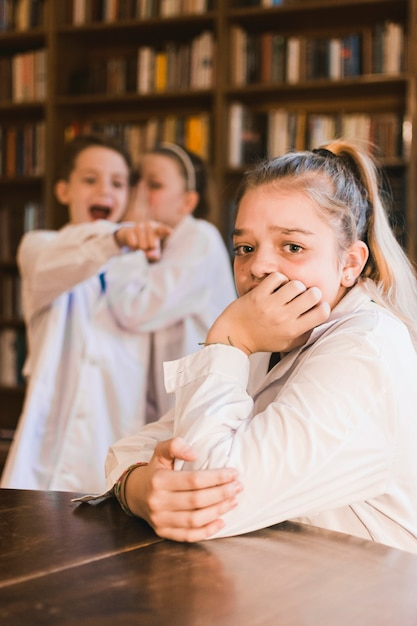 Bullies gossiping and mocking young crying girl Free Photo