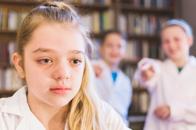 Bullies laughing at little crying girl Premium Photo