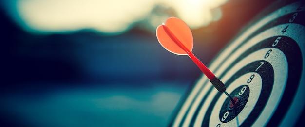 Яблочко бросает стрелу красного дротика в центр выстрела Premium Фотографии