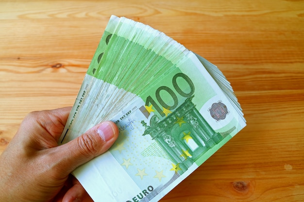 Bunch of 100 euro banknotes in man's hand with wooden table in the backdrop Premium Photo