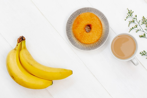 Bunch of bananas and doughnut top view Free Photo