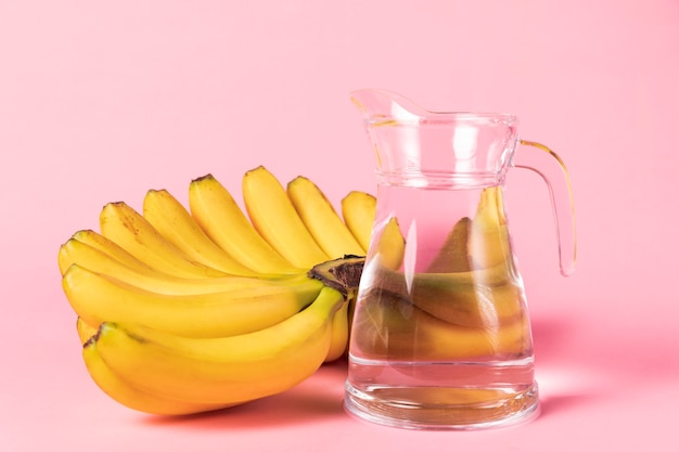 Bunch of bananas with jug of water Free Photo