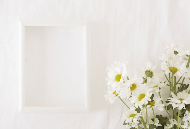 Bunch of beautiful flowers on green stems near frame Free Photo
