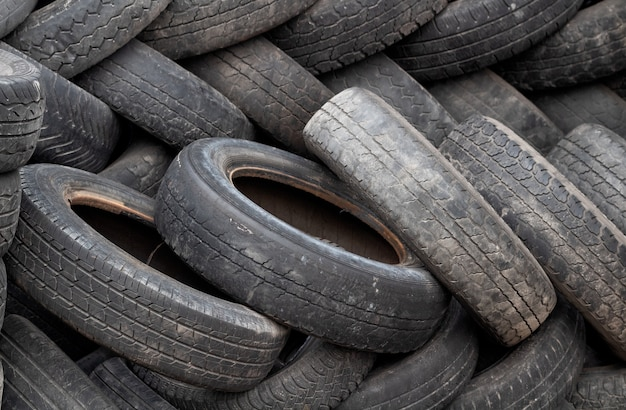 A bunch of dump tires from used cars. environmental pollution. Premium Photo
