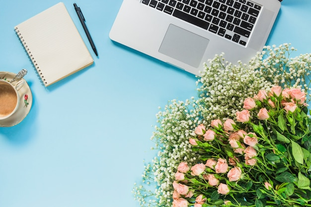 Bunch of flowers; coffee cup; spiral notepad; pen and laptop on blue background Free Photo
