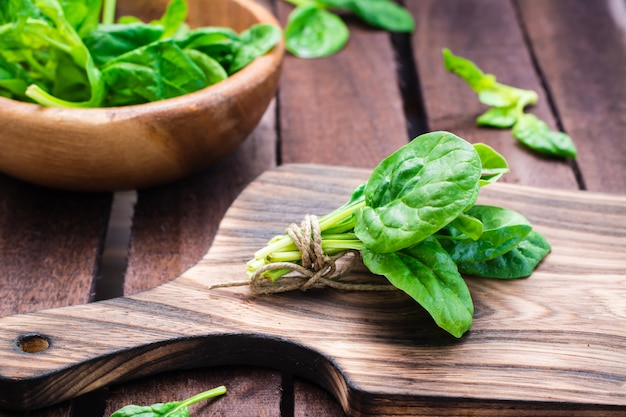 A bunch of fresh baby spinach leaves on a cutting board and spinach leaves in a bowl on a wooden table Premium Photo