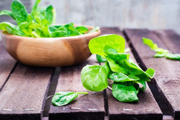 Bunch of fresh baby spinach leaves and spinach leaves in a bowl on a wooden table Premium Photo