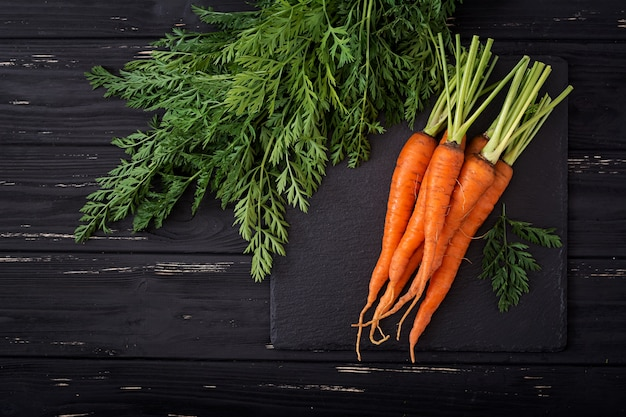 Bunch of fresh carrots with green leaves on wooden background.flat lay. top view Premium Photo