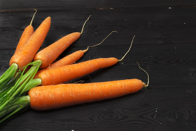 Bunch of fresh carrots with green leaves on wooden table Premium Photo