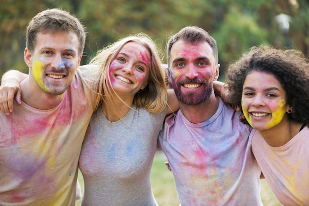 Bunch of friends smiling and posing with painted faces at festival Free Photo