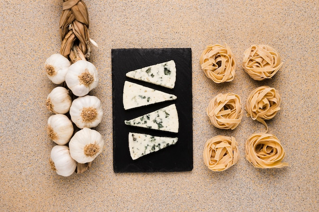 Bunch of garlic bulbs; cheese slices on tray and raw pasta arranged in row over marble wallpaper Free Photo
