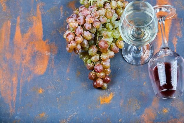 Grappolo d'uva e bicchieri di vino sull'azzurro. Foto Gratuite