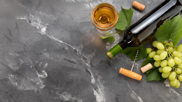 Bunch of grapes with bottle of wine on marble background Free Photo