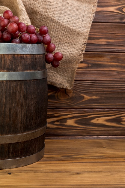 Bunch of grapes on wooden barrel Free Photo