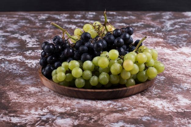 Un grappolo di uva verde e rossa in un piatto di legno Foto Gratuite