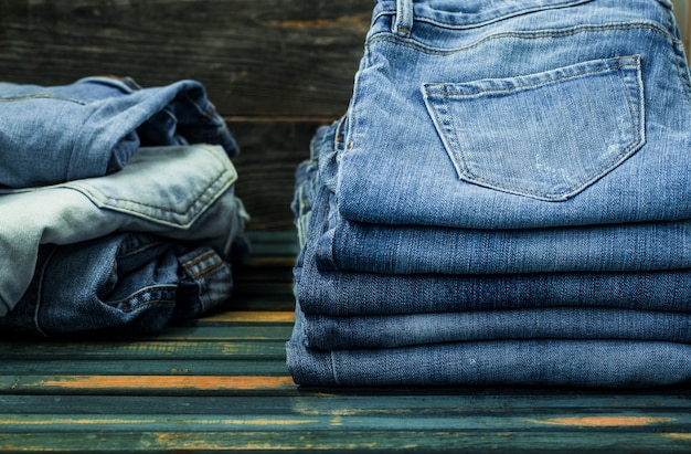 Bunch of jeans on wooden wall, fashionable clothes Free Photo