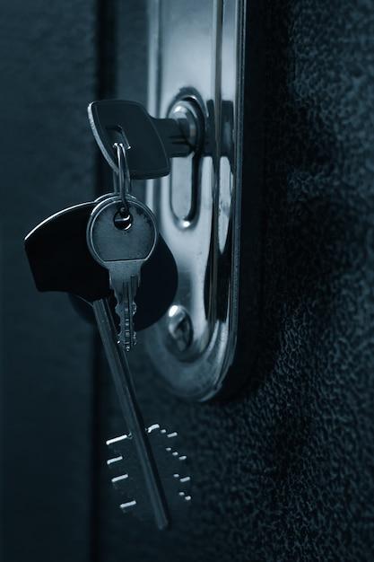 Bunch of keys in the keyhole of the door Premium Photo