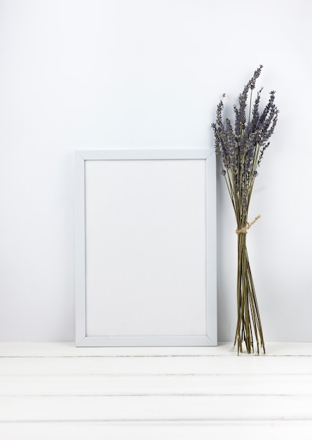 Bunch of lavender flowers with empty frame on wooden desk Free Photo