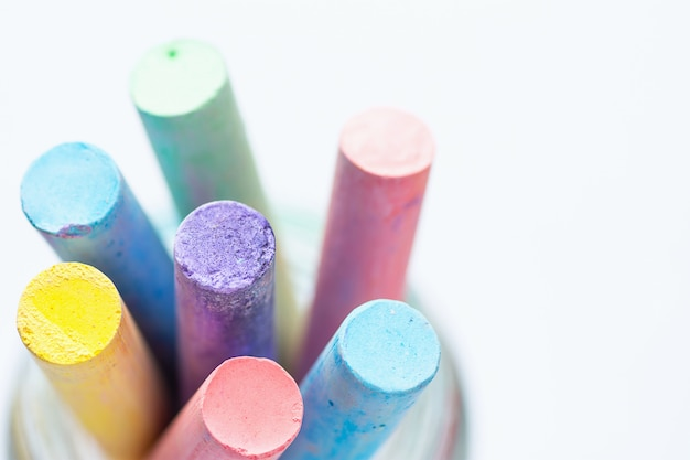Bunch of multicolored chalks crayons in pencil cup. top view white background. Premium Photo