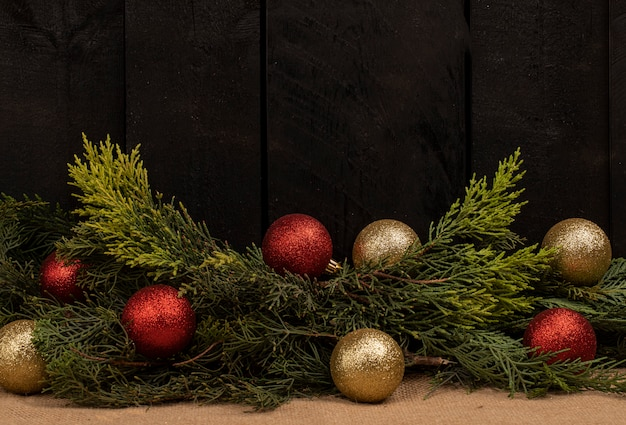 A bunch of oak tree branches and shining balls on a black wooden background Free Photo