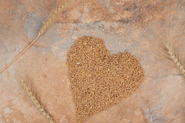 Гроздь ячменя в форме сердца на оранжевом фоне Бесплатные Фотографии