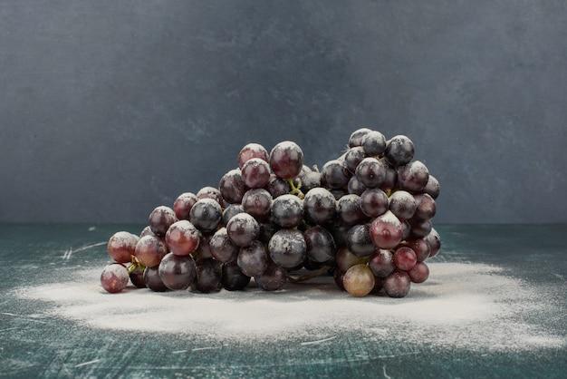 Гроздь черного винограда, украшенная пудрой на мраморном столе. Бесплатные Фотографии