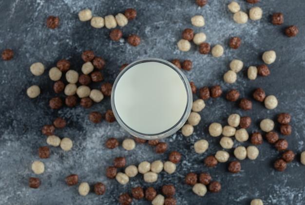 우유 한 잔 주위에 흩어져있는 시리얼 공의 무리. 무료 사진