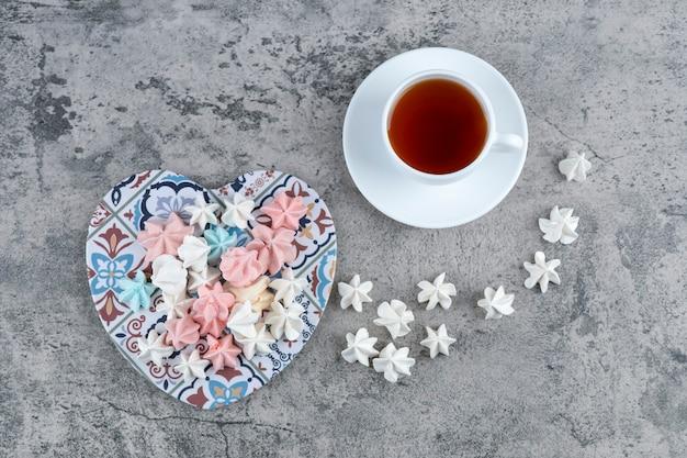 하트 모양의 삼발이와 차 한잔에 다채로운 머랭 사탕 무리. 무료 사진