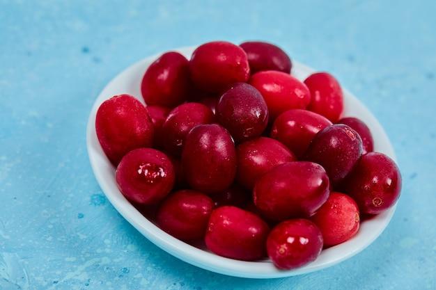 Букет из ягод кизила на белой тарелке. закройте вверх. Бесплатные Фотографии