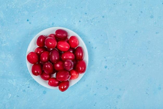 Букет из ягод кизила на белой тарелке. вид сверху. Бесплатные Фотографии