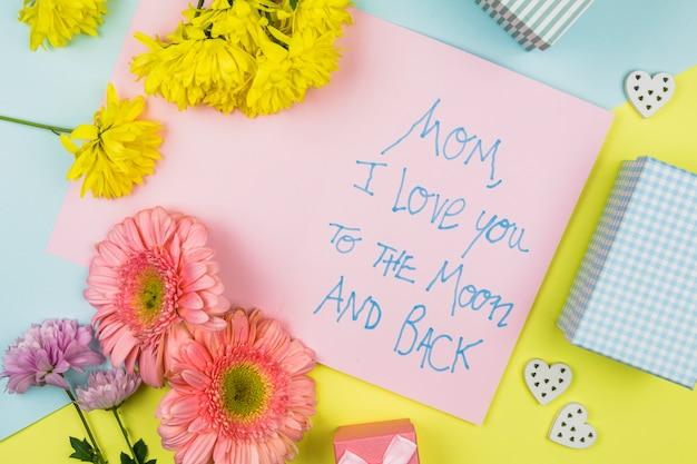 言葉、装飾用の心とプレゼントボックスと紙の近くの新鮮な花の束 無料写真