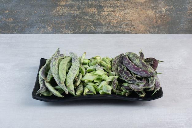 Букет из зеленой фасоли на черной тарелке. фото высокого качества Бесплатные Фотографии