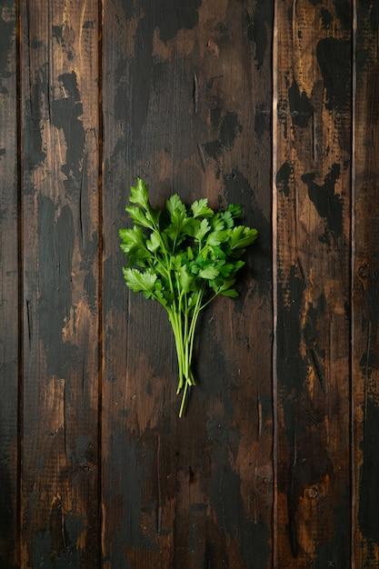 木製の素朴なテーブルに緑のパセリの束。上面図。 Premium写真