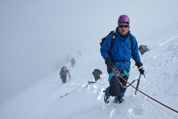 Куча альпинистов или альпинистов поднимается на вершину заснеженной горы Premium Фотографии