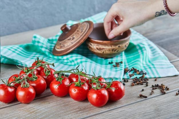 나무 테이블에 그릇에서 정향을 복용 분기와 여자 손으로 토마토의 무리 무료 사진