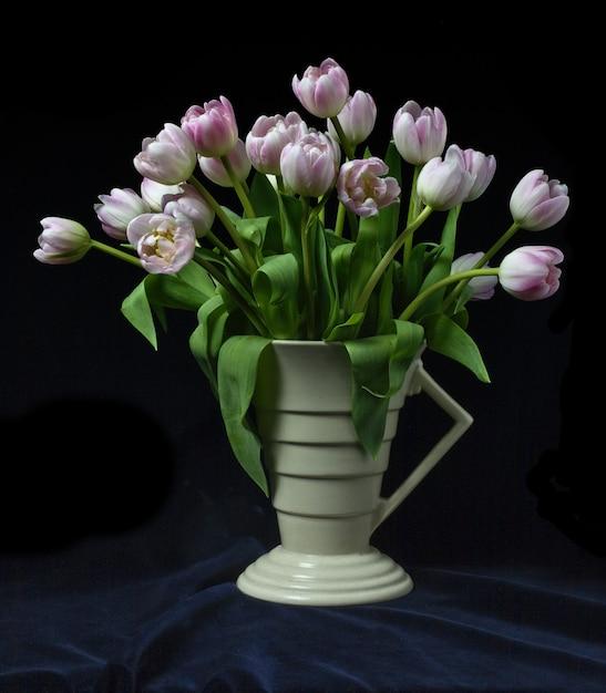 黒い背景とアールデコの花瓶のチューリップの束 無料写真