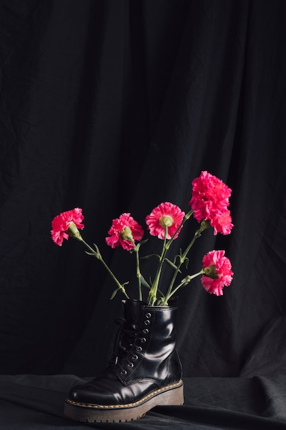 Bunch of pink blooms in dark boot Free Photo
