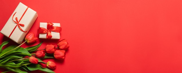 Bunch of red tulips and gift boxes with red ribbons on a red background. Premium Photo