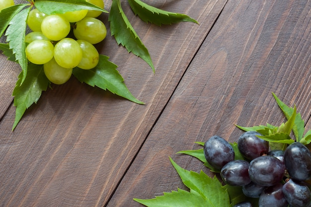 Bunch of red and white grapes on wooden table background Premium Photo