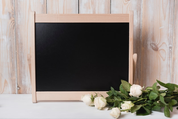 Bunch of roses with wooden small blackboard on white desk Free Photo