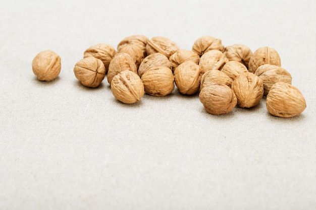 Bunch of round whole walnuts on a very light blurred fabric background. Premium Photo