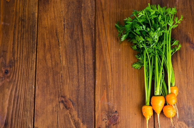Bunch of small, round carrots (parisian heirloom carrots) on wooden background. Premium Photo
