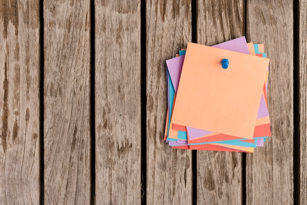 Bunch of sticky notes attached with blue push pin on wooden table Free Photo