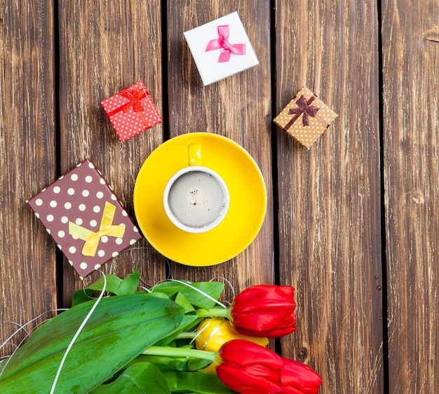 Bunch of tulips, cute gifts and cup of coffee on the wonderful brown wooden background Premium Photo