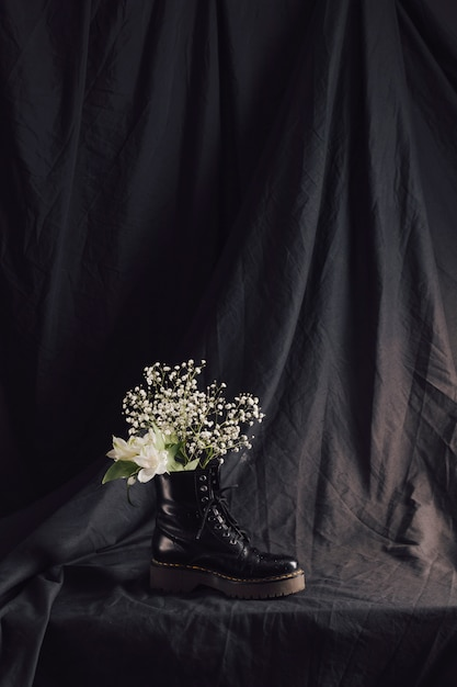 Bunch of white blooms in dark leather boot Free Photo