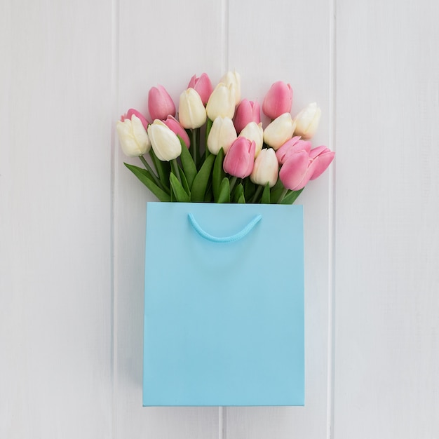 Bunch of yellow tulips in cool blue shopping bag Free Photo