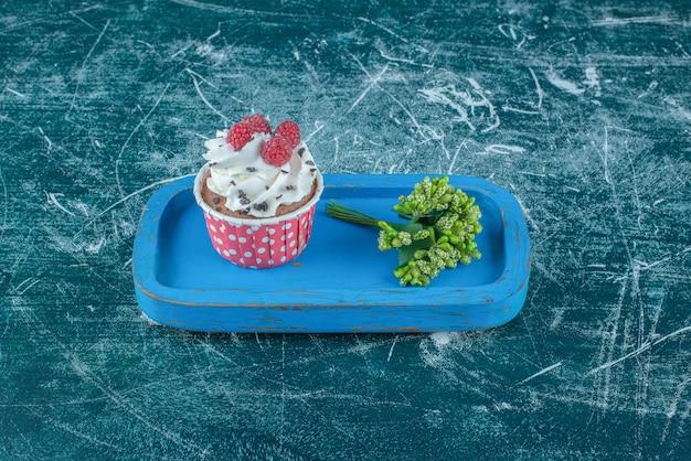 Fascio di boccioli di fiori e un cupcake su un piatto di legno su sfondo blu. foto di alta qualità Foto Gratuite