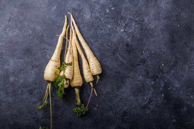 Bundle of fresh organic parsnip  over gray texture surface . Premium Photo
